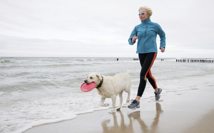 A woman jogging with her dog on the beach.